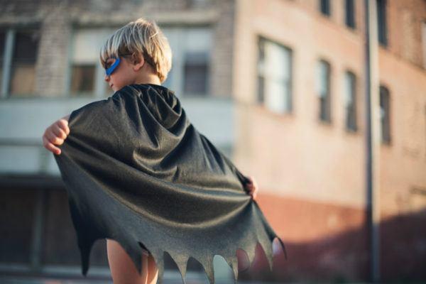 En dreng med superheltemaske og kappe - fordi tekstforfattere er en slags helte.
